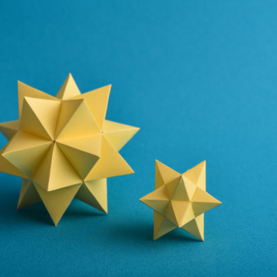 Two handmade yellow paper polyhedrons on a blue background.